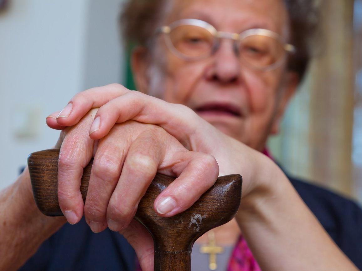 Symbolbild: Alte und junge Hand mit Gehstock