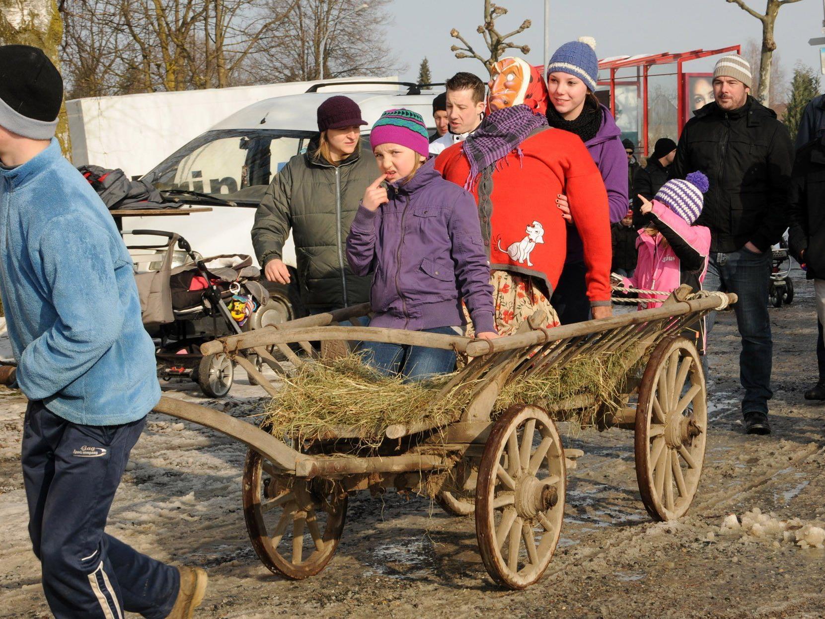 Auf dem Leiterwagen wird die Hexe zum Brugger Funken in Höchst gefahren, Julia hält sie fest.