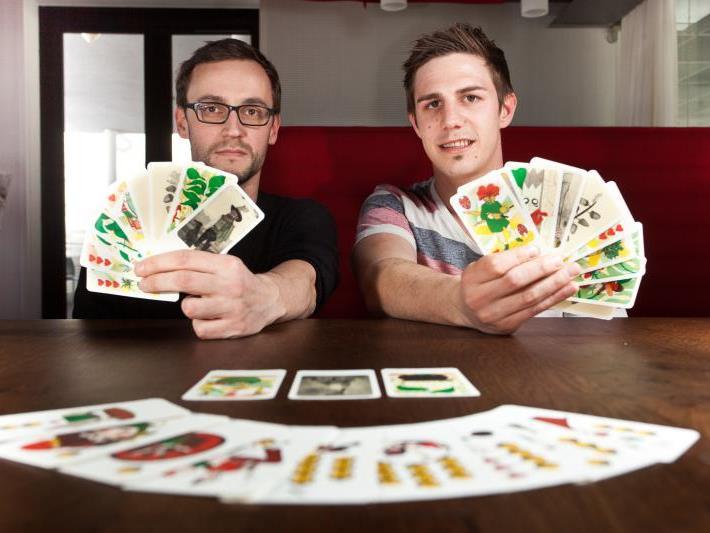 """Christian Feurstein vom """"Landjäger"""" (l.) und Simon Bischof von den Sporoneggarn mit einem """"Prototyp"""" der neuen Karten."""