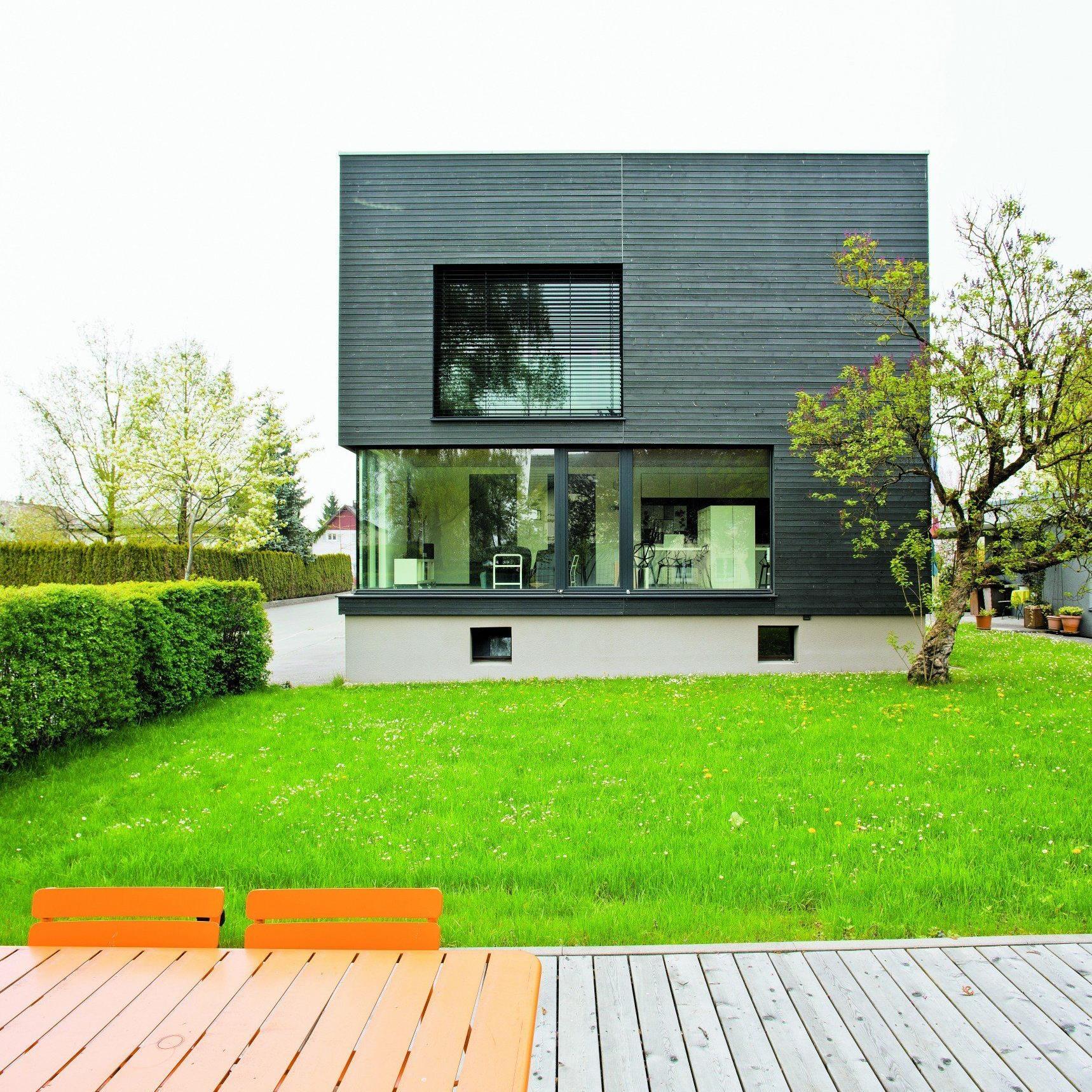 Das dunkle Grau lässt den Materialeindruck zwischen Holz und Sichtbeton schwanken. Die Reduktion der Form steigert jede Liniatur und jede Öffnung zu bedeutsamen Gestaltungselementen.