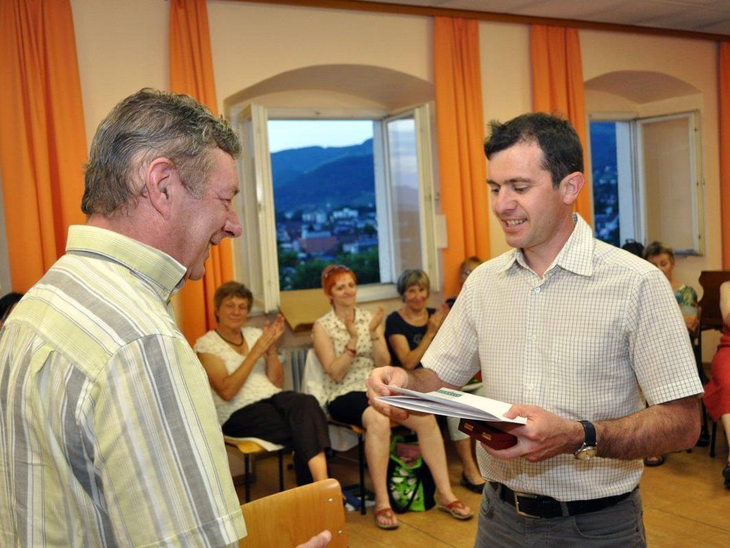 Bürgermeister Martin Summer dankt Langzeit-Chorleiter Gebhard Mathis für seine geleistete Arbeit.