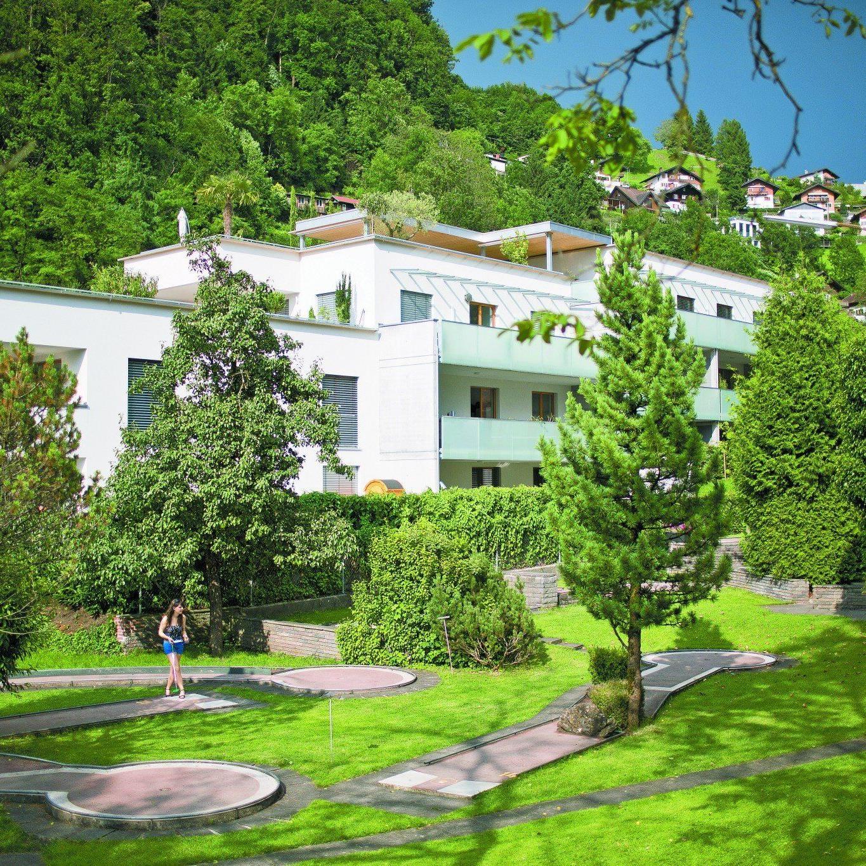 Das reiche Grün rund um das Haus ergänzt sich mit den klaren Flächen aus Mattglas, hellgrauem Sichtbeton und der weißen Putzfassade.