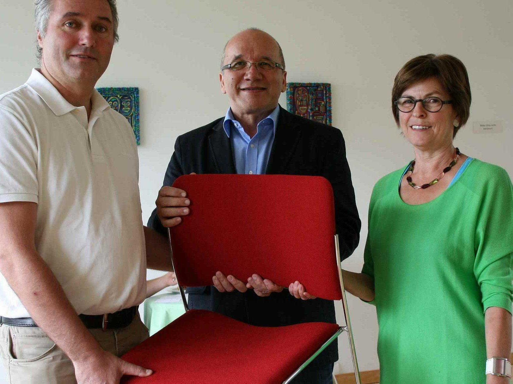 Moderner Klassiker in Rot: Freundeskreis-Obmann Christian Hörl (li.) und Vorstandsmitglied Irmgard Konrad bei der offiziellen Übergabe an Hausleiter Josef Kittinger.