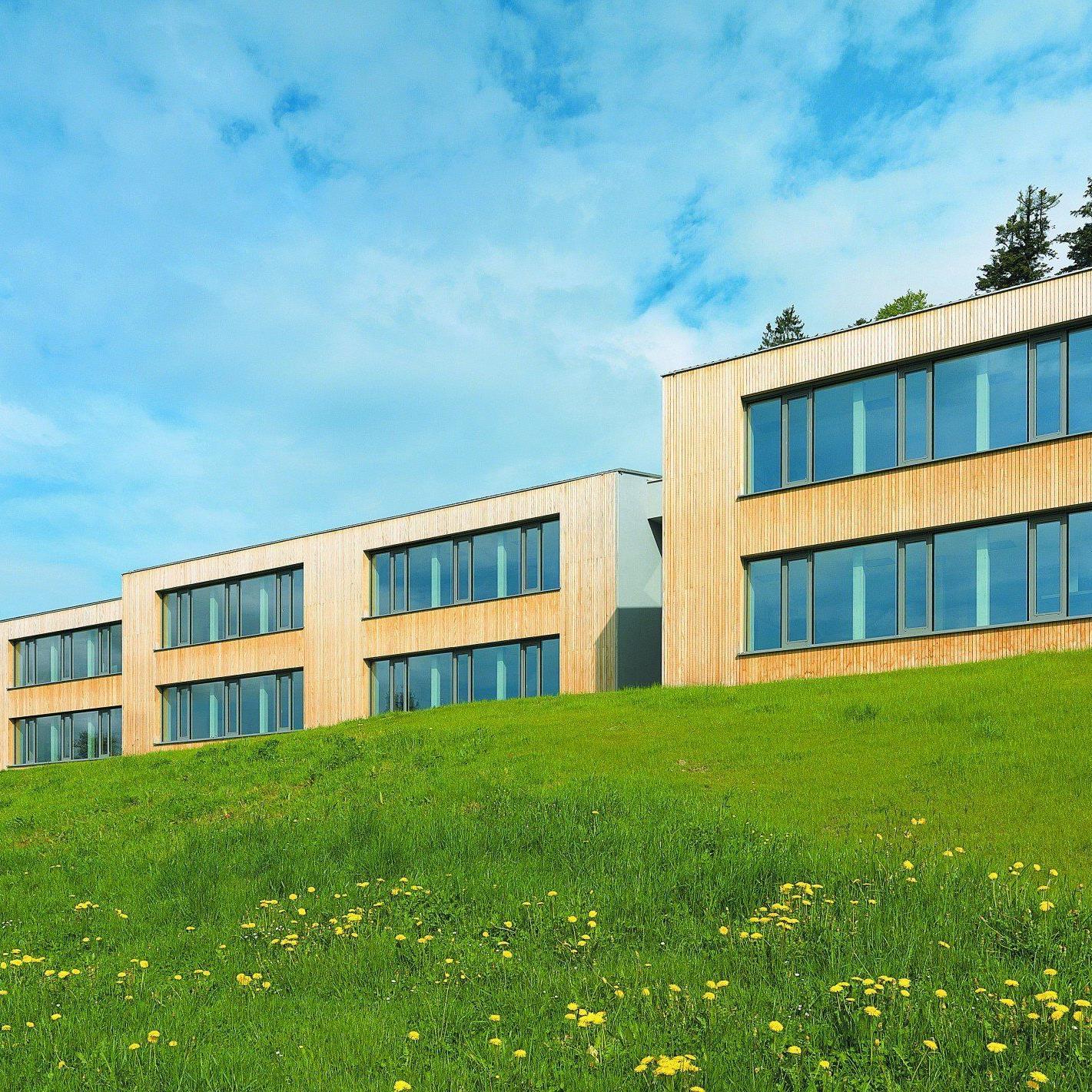 Tribünentreppe. Eine Komposition kräftiger Baukörper und freier Durchblicke, die in Dachform und Stufen der großen Treppe die Landschaft spüren lassen.
