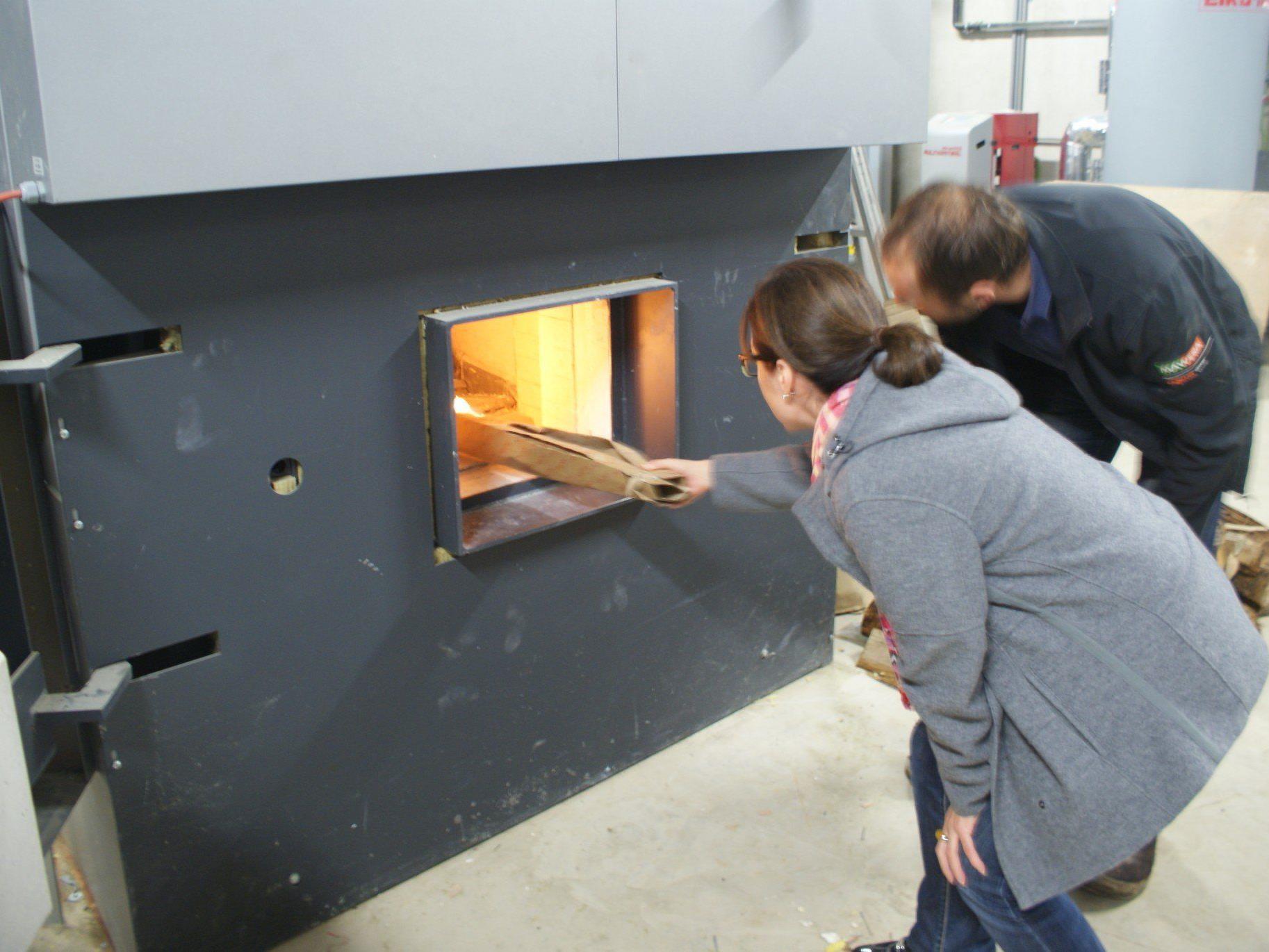 GF Tschütscher beim Anzünden des Biomasseheizkessels.