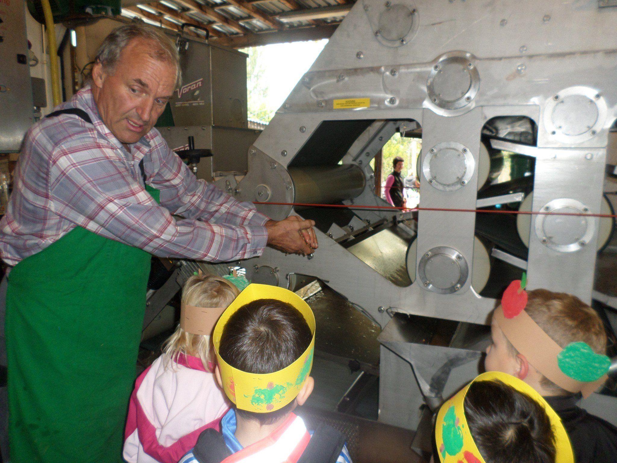 Paul Böckle zeigt den Kindern wie Most gemacht wird.