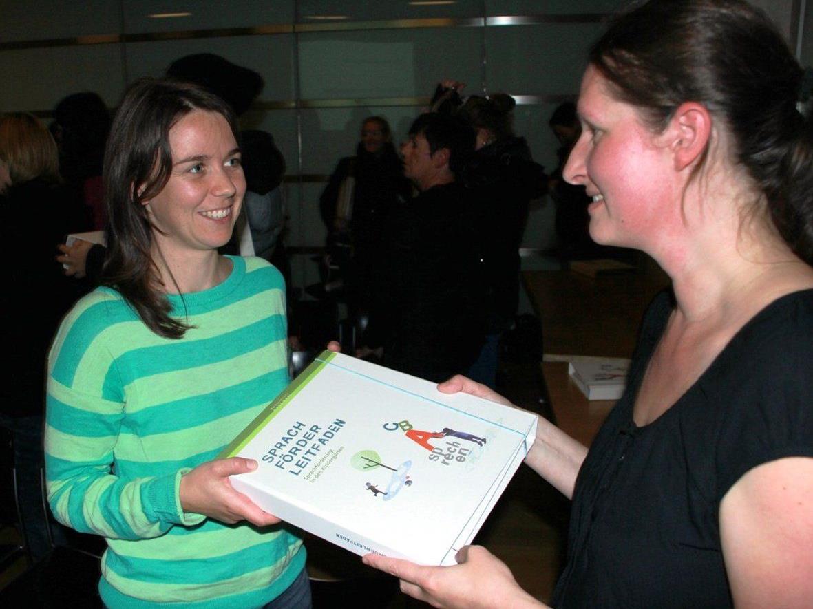 BU: Projektleiterin Melanie Schär (rechts) bei der Übergabe des Sprachförderleitfadens an Susanne Bergauer, Kindergartenpädagogin im Kindergarten Montfort.