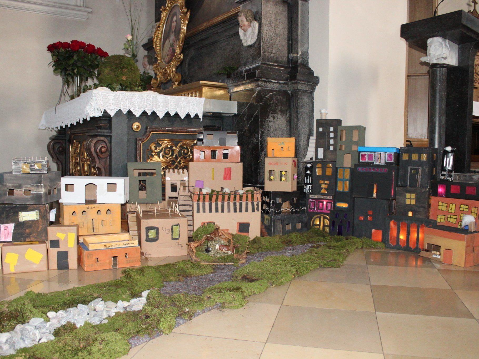 Die Kinder schaffen mit ihren Häusern eine Herberge für das Jesukindlein in der Pfarrkirche Au.