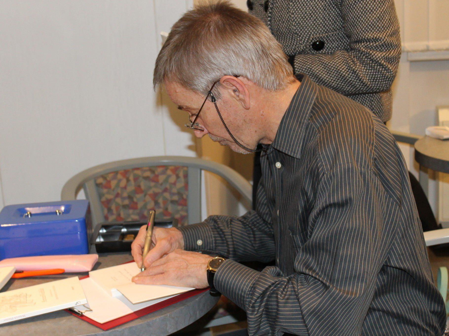 Der Autor beim Signieren seines Werkes