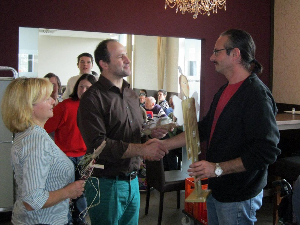 Obfrau Gertrud Schütz und Jürgen Feistenauer (rechts), Leiter der Werkstätte Hohenems, bedanken sich mit Geschenken bei Gastgeber Gebhard Hopfner