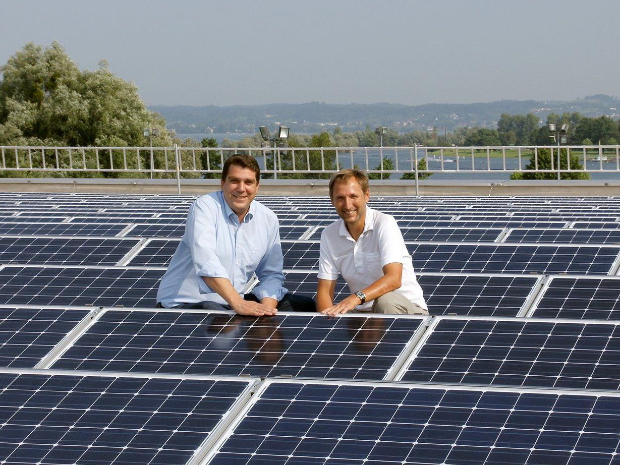 Harald Köhlmeier und Gemeinderat Peter Bildstein inmitten von Photovoltaikmodulen der Sporthalle.