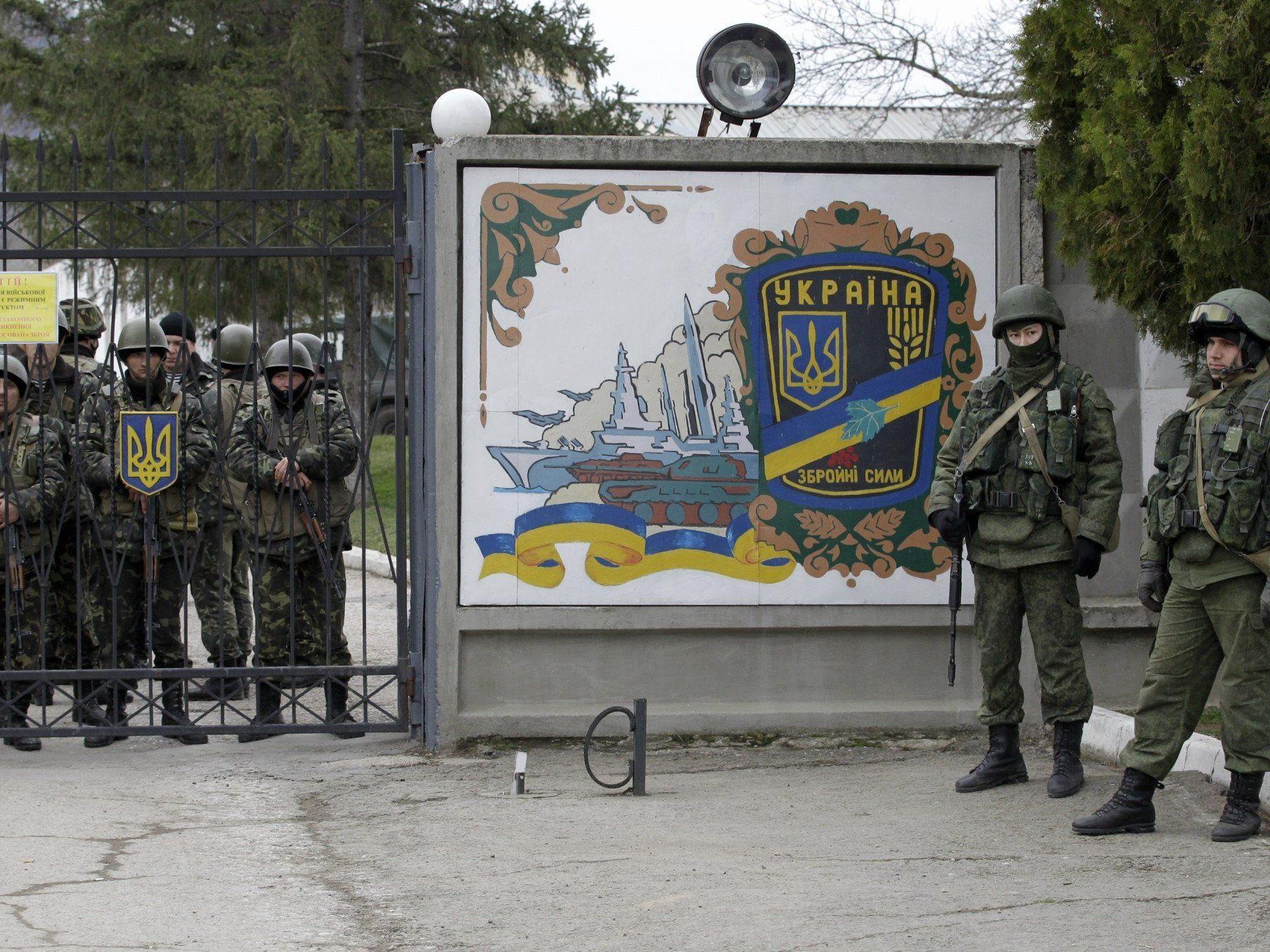 Unidentifizierte Truppen (r.) hindern ukrainische Truppen (l.) am Verlassen ihres Stützpunktes.