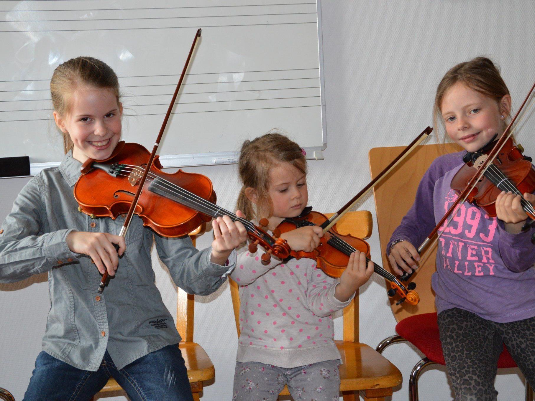 Die jungen Geigenspielerinnen Josefa und Lina nehmen Johanna in die Mitte