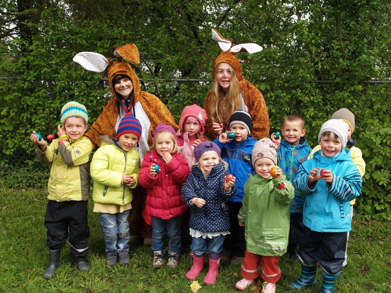Tanja und Laura von der Pfadfindergruppe Rankweil mit einigen Kindern beim Ostereiersuchen.