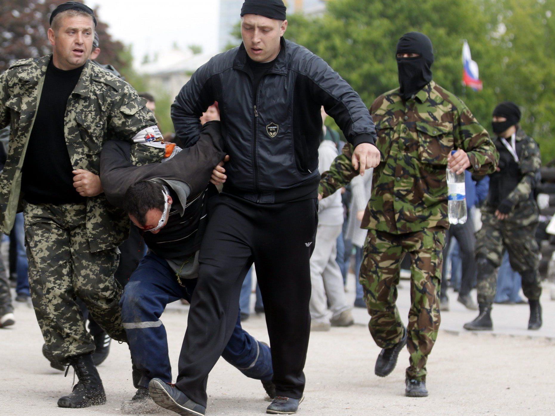 Prorussische Aktivisten schleppen einen Unbekannten in das besetzte Verwaltungsgebäude von Donetsk..