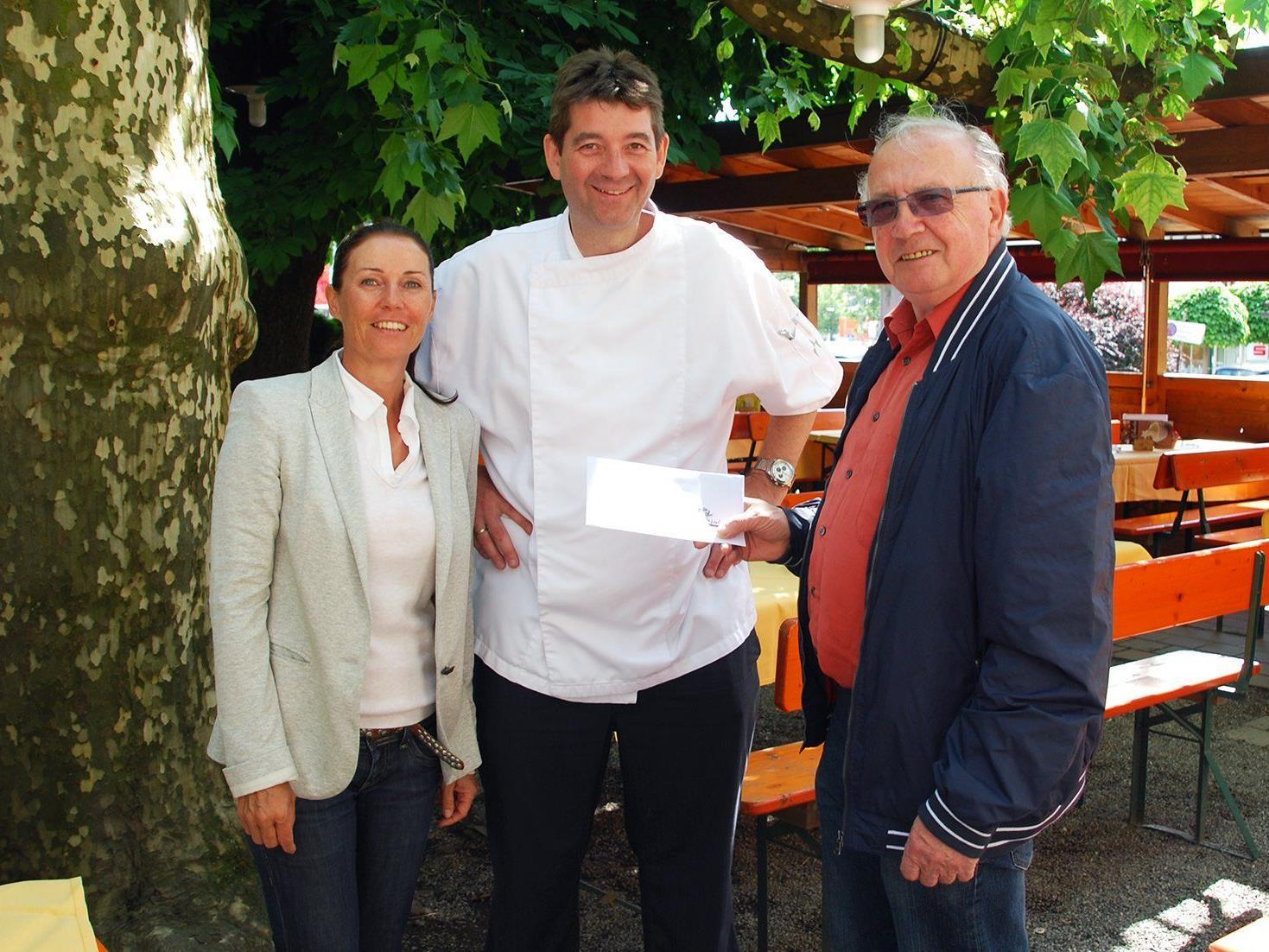 Carolin Frei (GF Erlebnis Rankweil) und Roland Vith (Rankweiler Hof) übergeben den Gutschein an Alexander Weber aus Feldkirch.