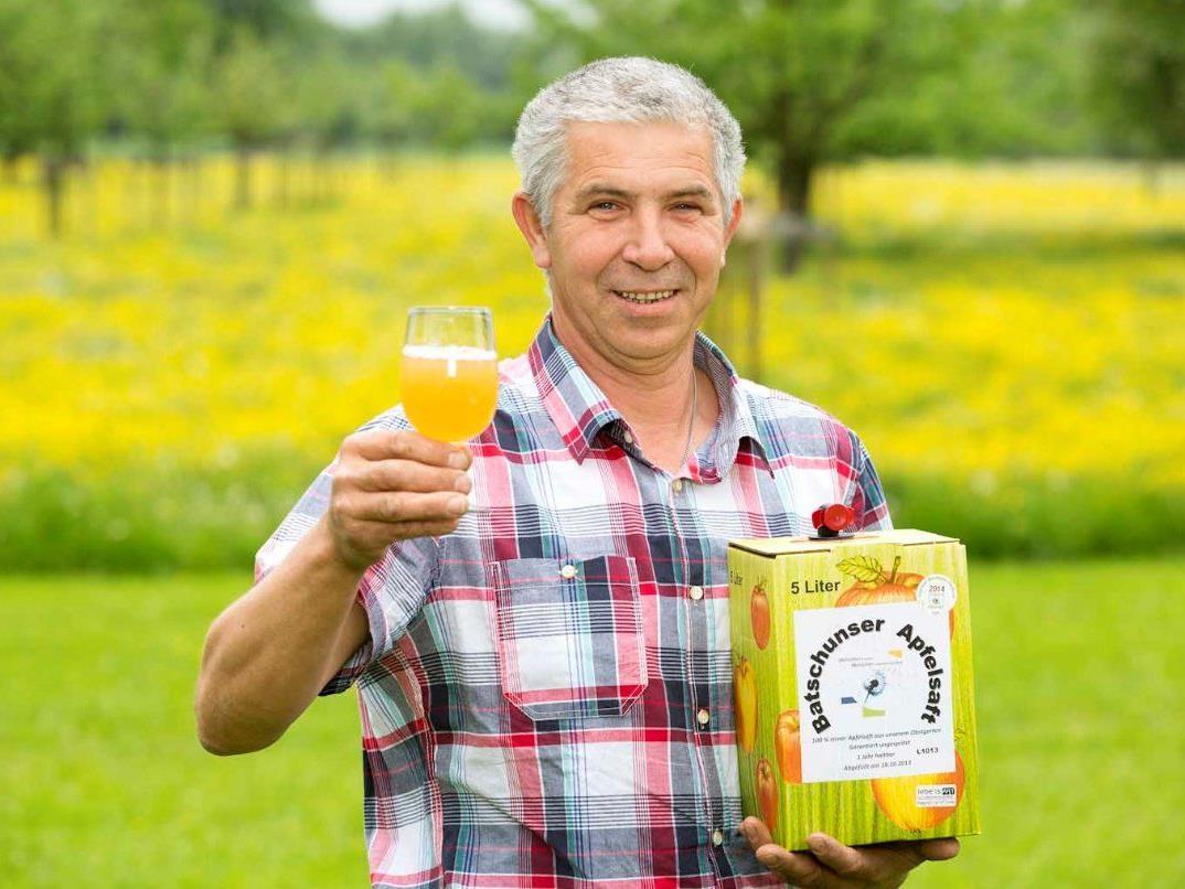 """Werkstätten-Mitarbeiter Michael Stumpf ist stolz auf den """"Batschunser Apfelsaft""""."""