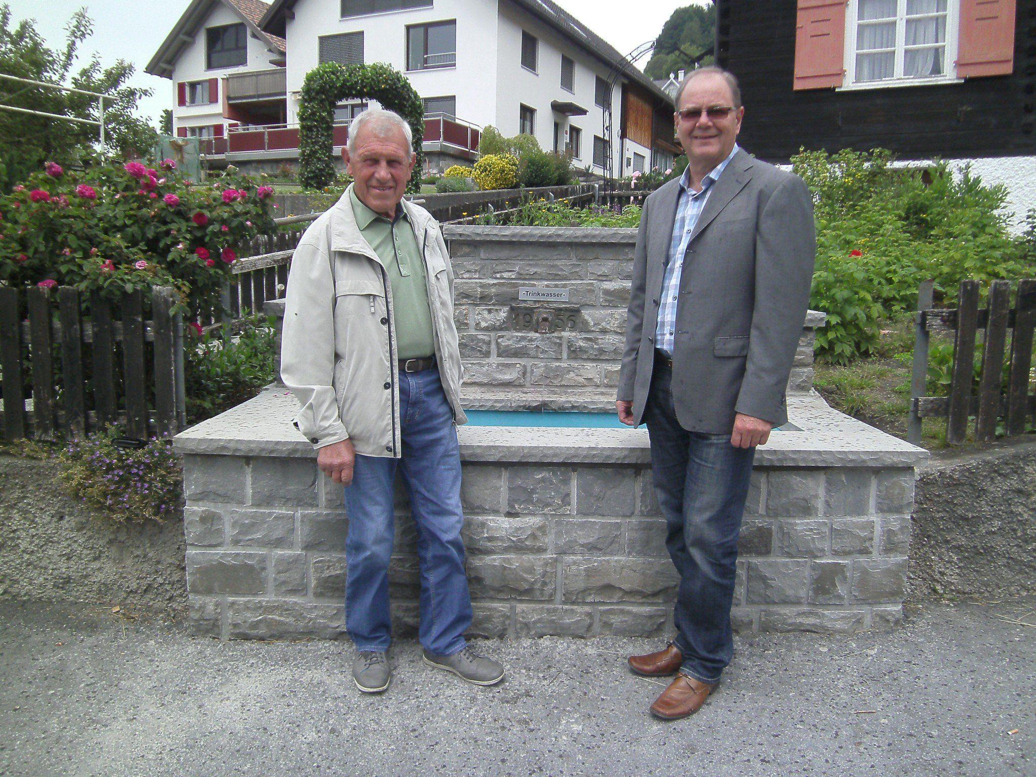 Bgm. Reinhard Nachbaur (re.) und Steinmaurer Oswald Nägele vor dem neu sanierten Dorfbrunnen.