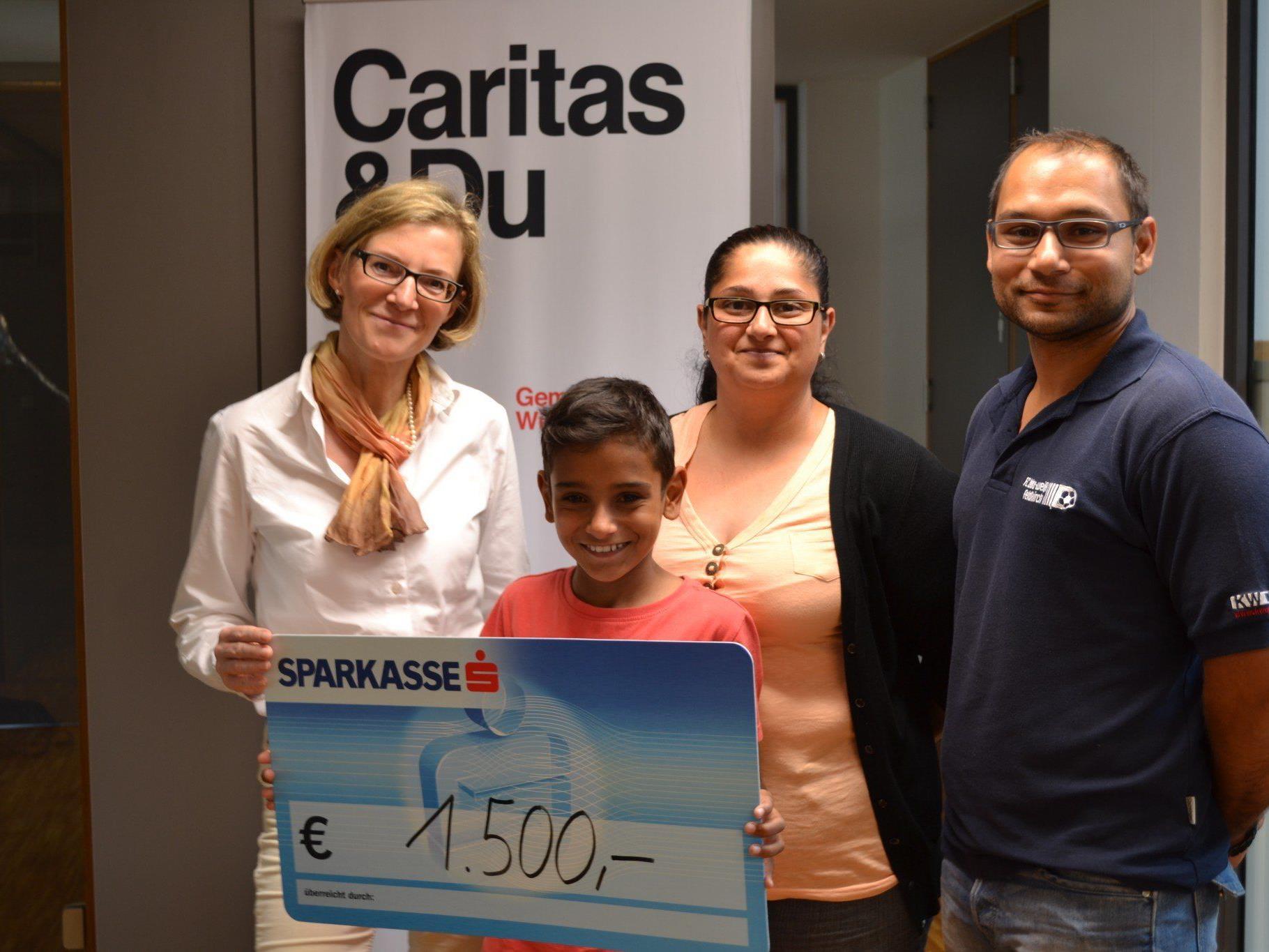 Sanja und Miroslav Sretenovic mit Sohn und Caritas-Mitarbeiterin Doris Ramspeck (links im Bild) bei der Scheckübergabe.