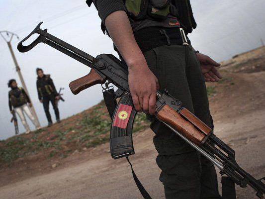 Mitglieder der Volksverteidigungseinheiten stehen Wache an einem Kontrollpunkt.