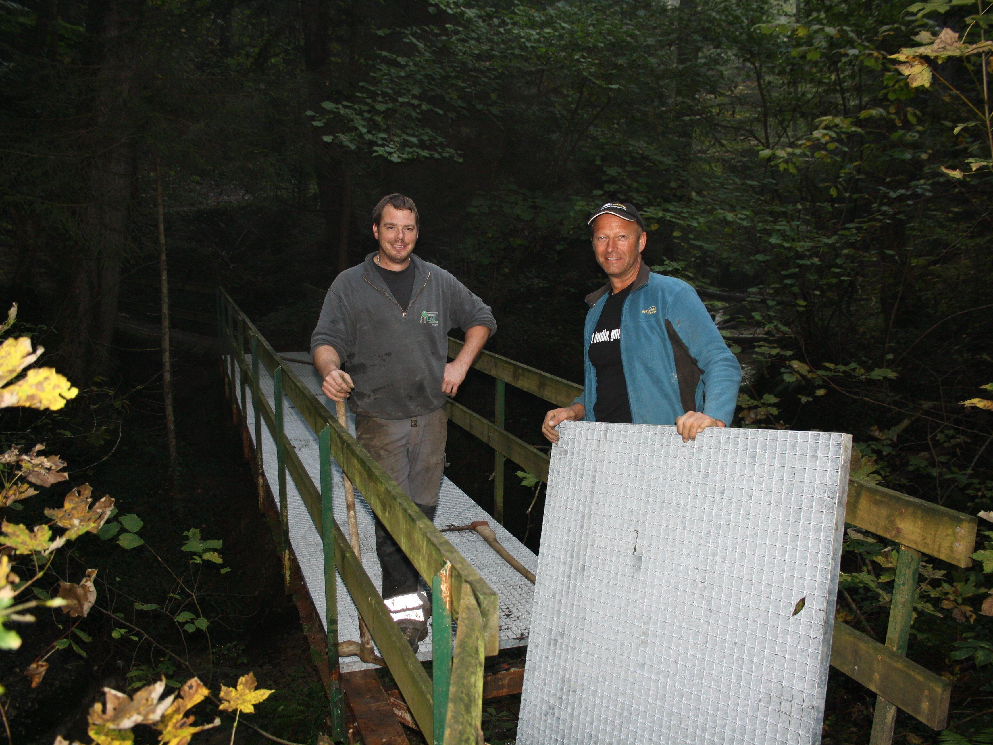 """Andreas Fessler und Roland Felder vom Wirtschaftshof haben auf dem """"Ruinen-Wanderweg Alt-Hofen"""" die Brücke über das Dorfbachgerinne erneuert."""