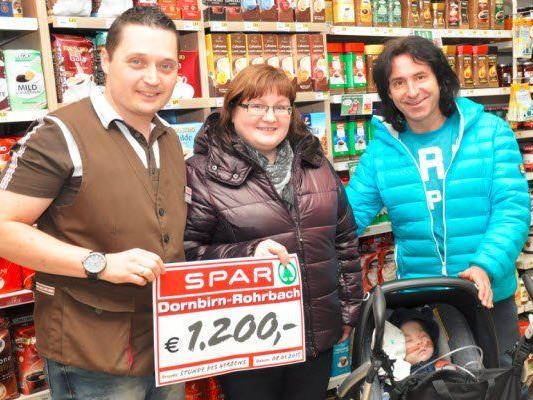 Marktleiter Martin Gmeiner (links) und übergibt den Scheck von insgesamt 1.200,- Euro an Joe Fritsche, Stunde des Herzens (rechts) und Cornelia Konzett mit ihrem Sohn Felix.