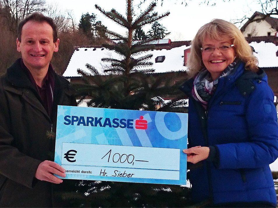 Sylvia Steinhauser vom Vorarlberger Kinderdorf freut sich über die verdoppelte Spende, die sie von Herrn Sieber entgegennimmt.