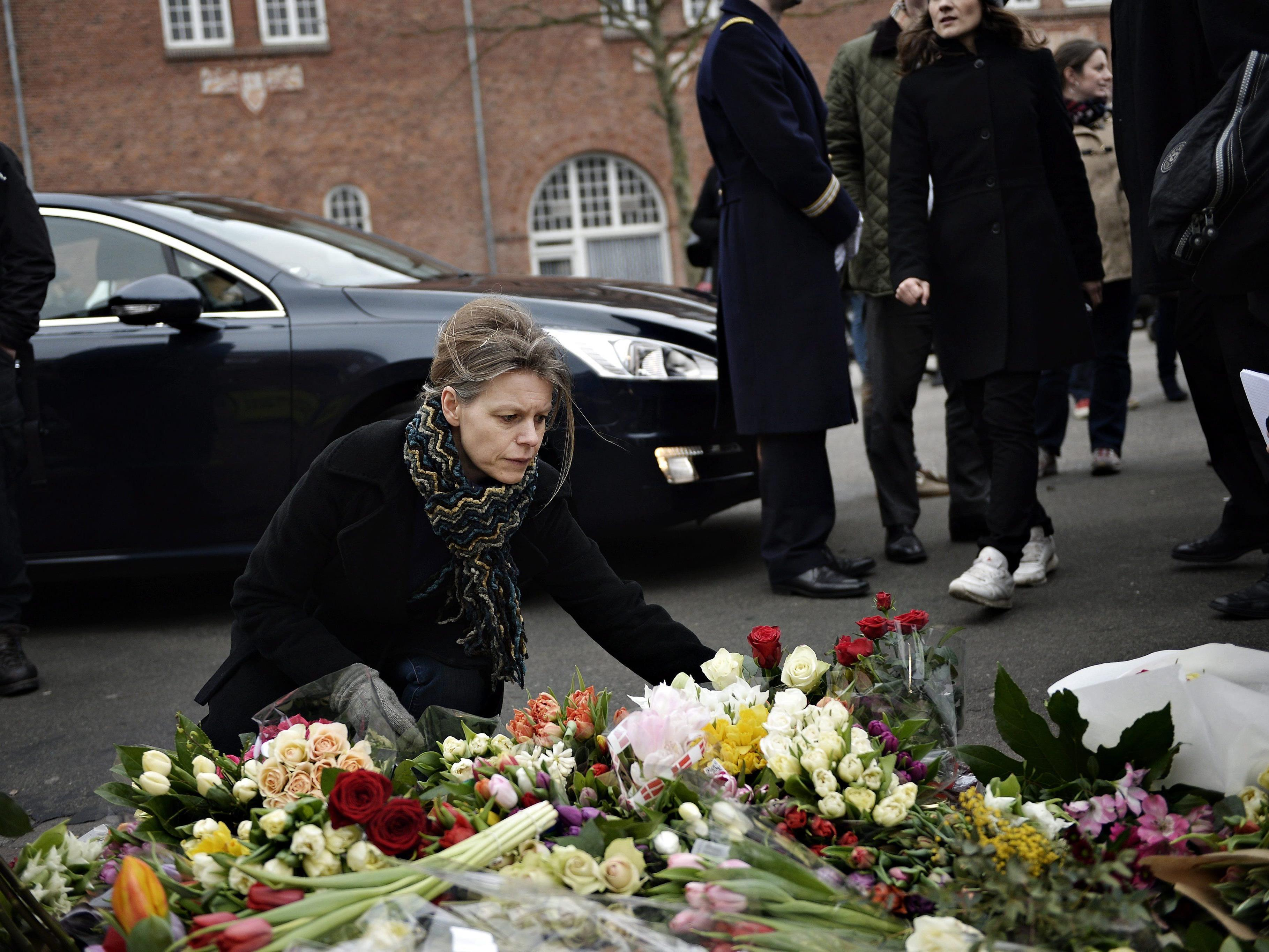 Eine Frau legt Blumen vor der Synagoge nieder, in der ein Wachmann erschossen wurde.