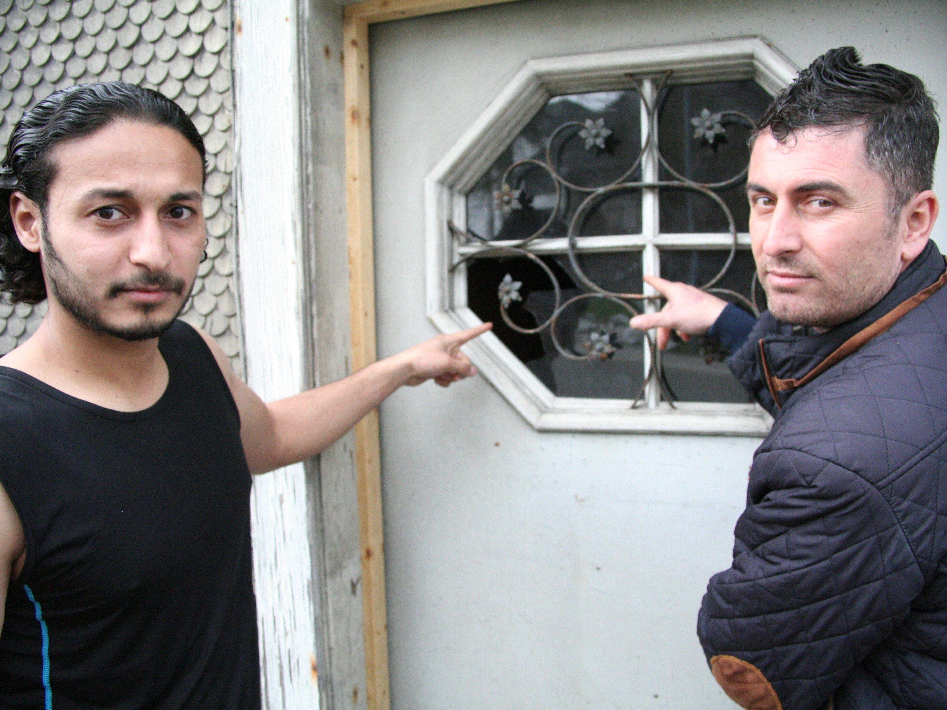Schockiert: Leith (l.) und Azad zeigen auf das eingeschlagene Fenster der Eingangstür.