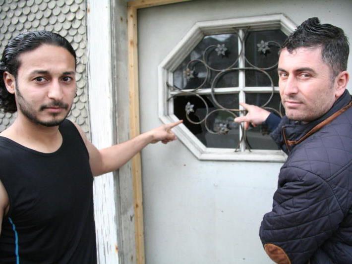 Bewohner des Asylheims zeigen die zerbrochene Scheibe