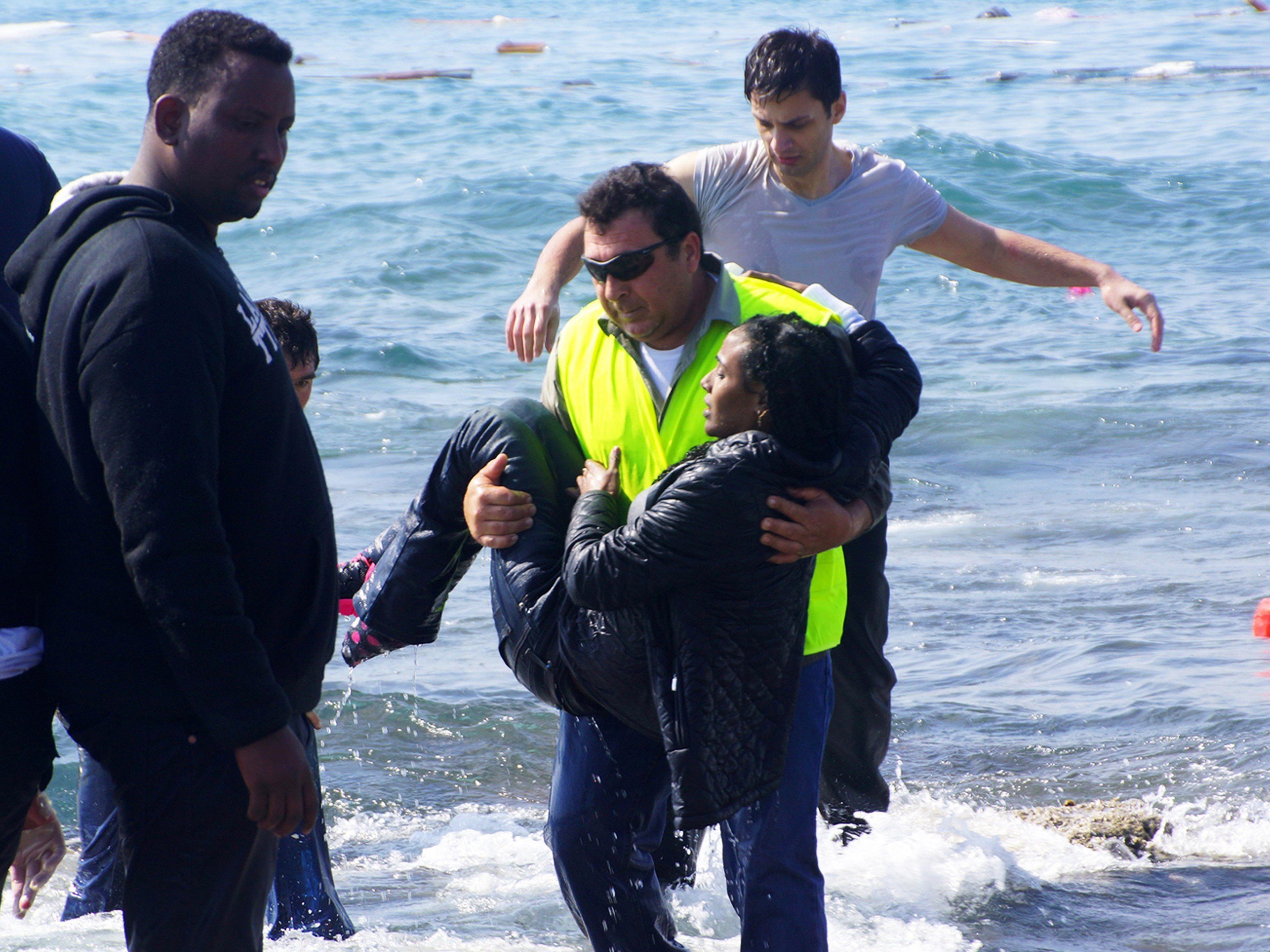 Ein Helfer rettet eine Frau aus den Fluten. Drei Schiffe mit Flüchtlingen sollen allein am Montag in Seenot geraten sein.