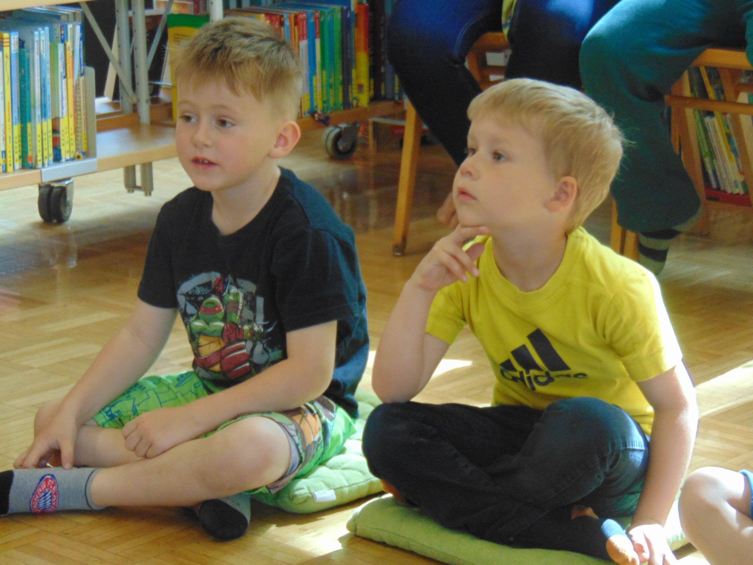Interessiert hören die Kinder beim Erzählen einer Geschichte zu