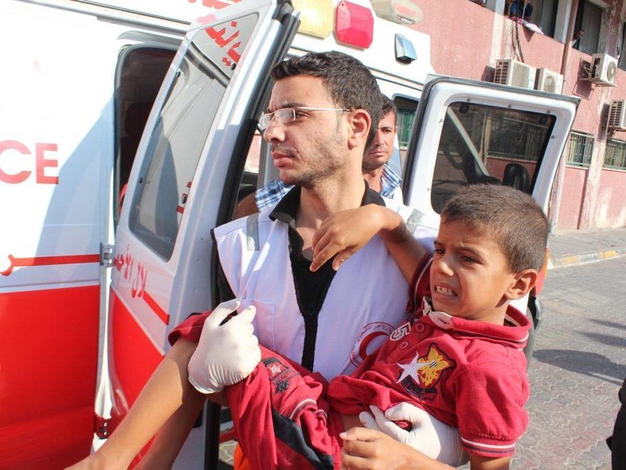 Gaza, Juli 2014: Mitarbeiter und Freiwillige des Palästinensischen Roten Halbmond leisten medizinische Versorgung und evakuieren die Verwundeten in Chan Yunis-Stadt, im südlichen Teil des Gazastreifens.
