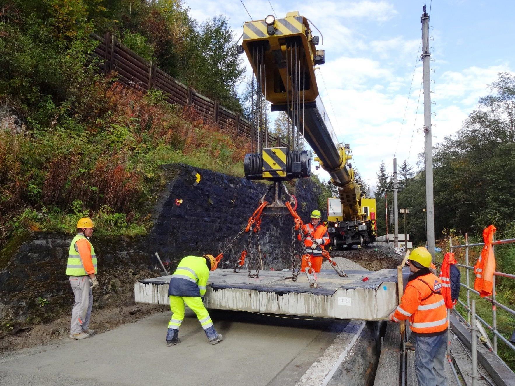In der Nacht von 20./21. Juni kommt auf der Arlbergbahn bei Landeck ein großer Schienenkran beim Ausbau der Hilfsbrücke zum Einsatz.