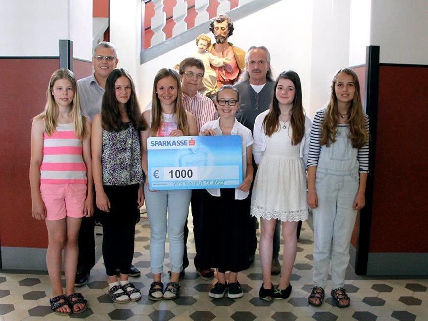 Schülerinnen, LehrerIn und Martin Lienert bei der Übergabe des Schecks.