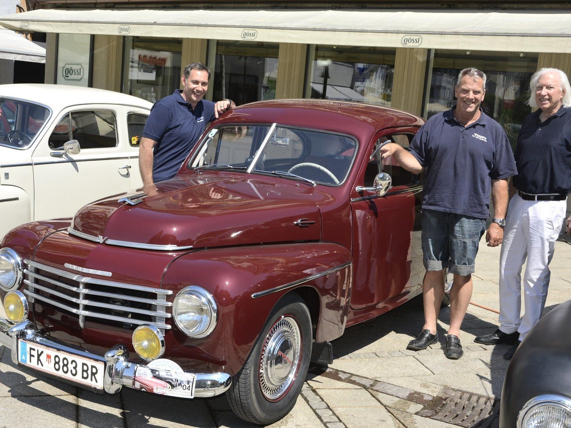 Thomas Niedermair und Jörg Knapp stellen sich neben Günter Drexel,  den stolzen Besitzer des ältesten Volvo-Modells aus dem Jahr 1953.