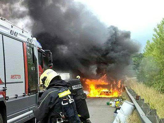 Ein Feuerwehrmann vor dem brennenden Pkw auf der A1