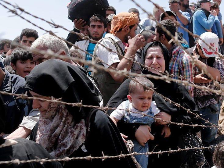 Flüchtlinge erreichen nach tagelangen Fußmärschen erschöpft die türkische Grenze.