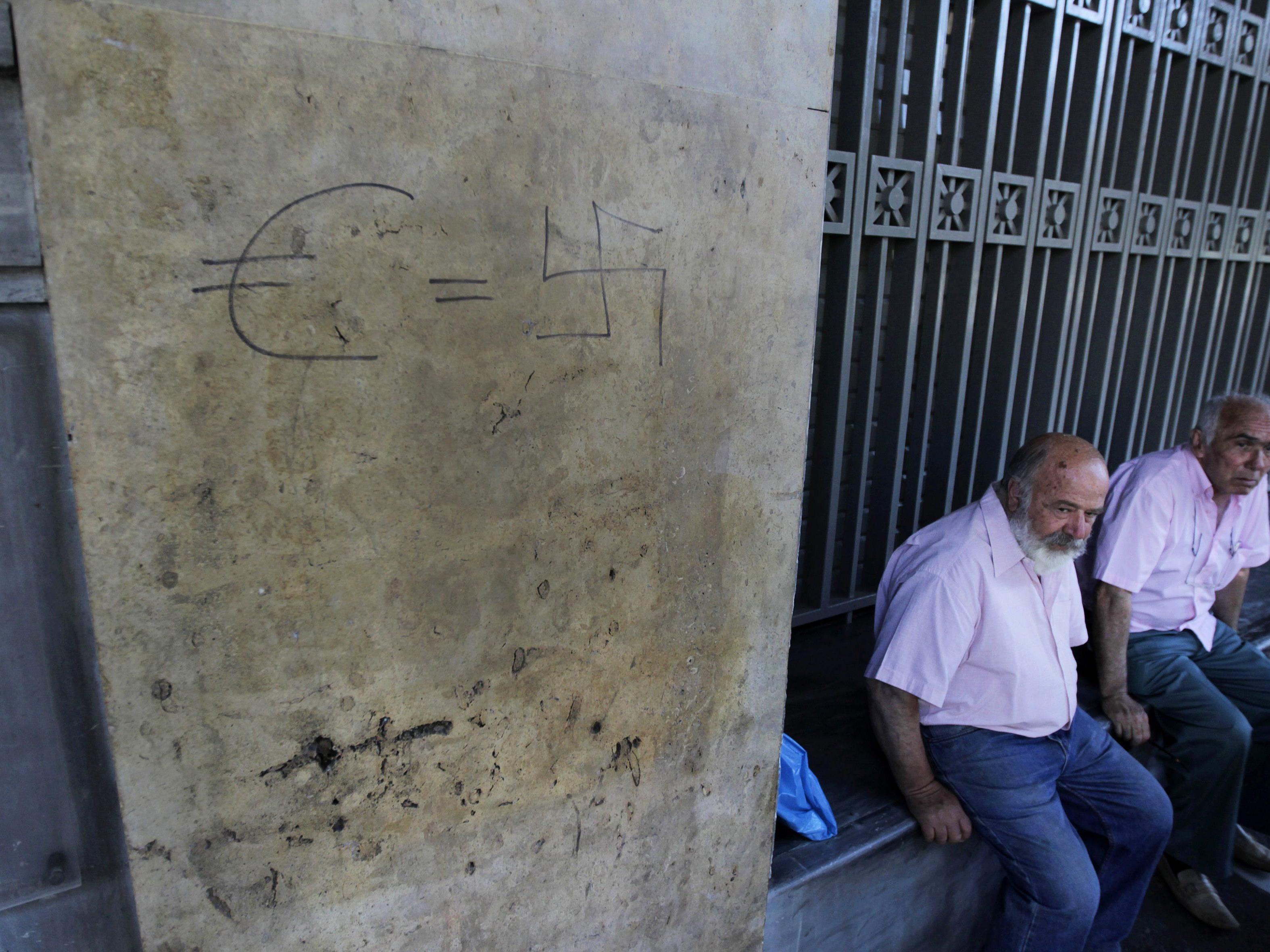 Zwei Pensionisten vor einer geschlossenen Bank. Ein Graffiti an der Wand setzt den Euro mit dem Nationalsozialismus gleich.