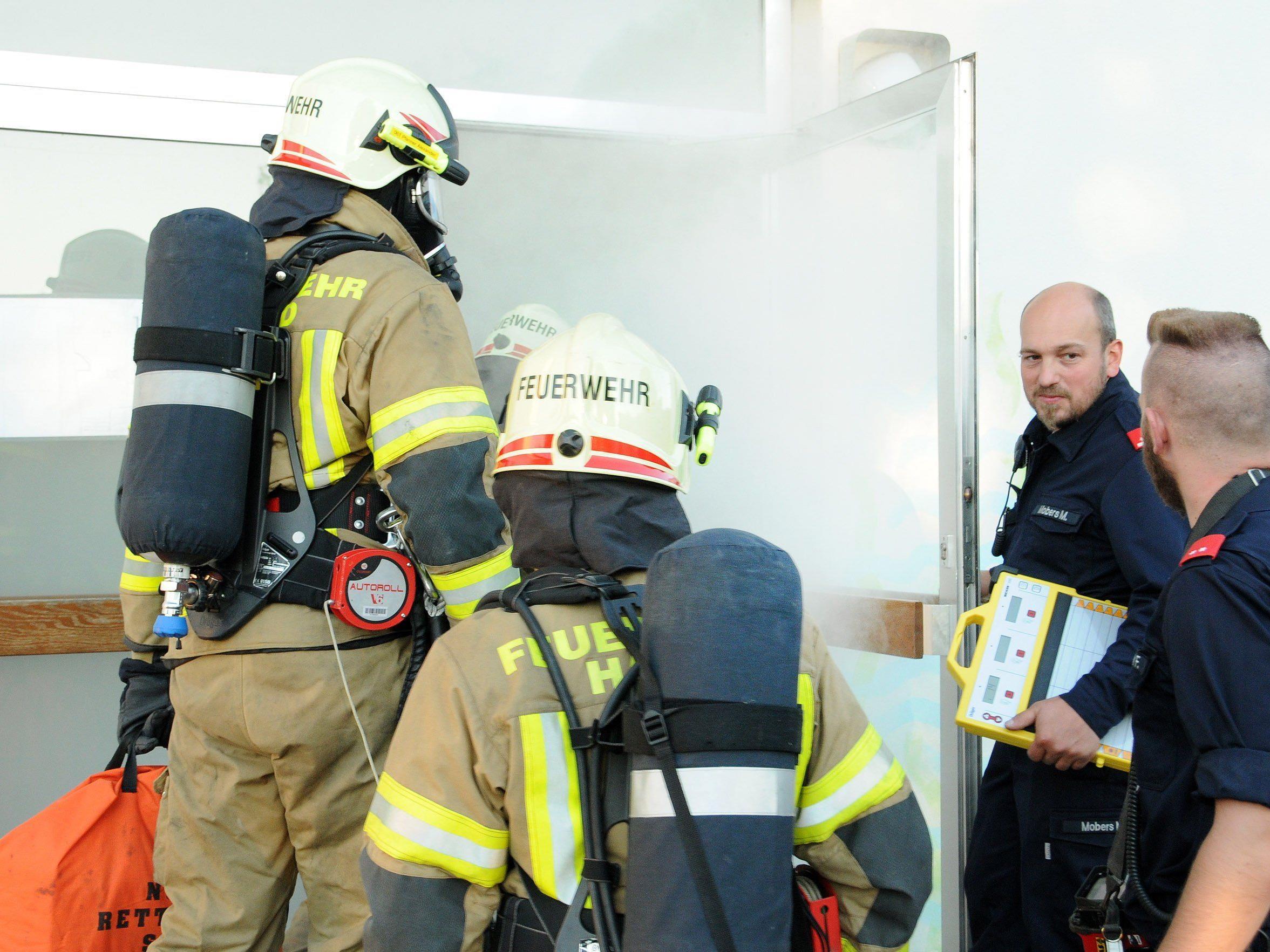 Feuerwehrmänner mit schwerem Atemschutz dringen in das völlig vernebelte Schulhaus ein.