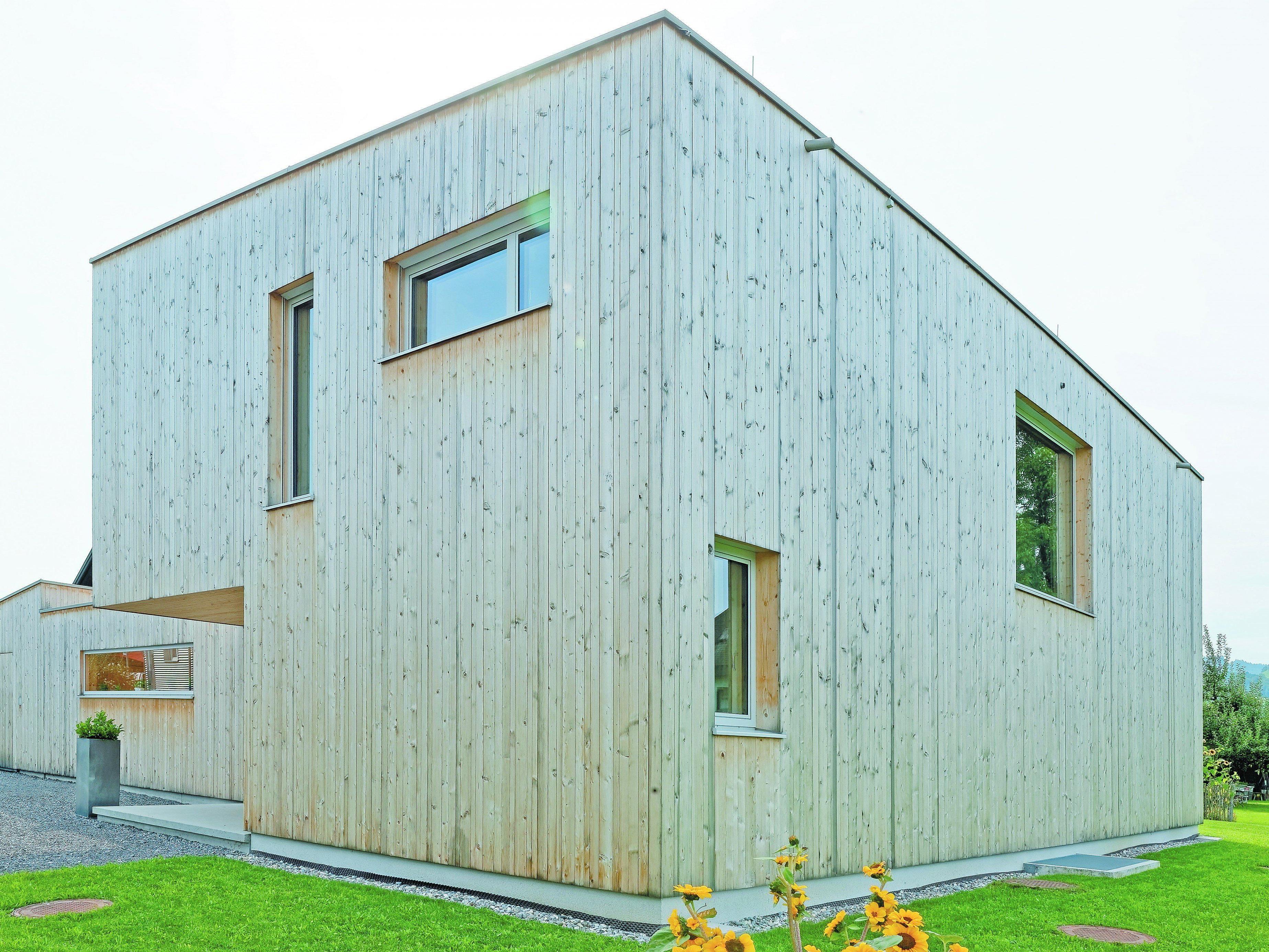 Fensterspiele Als raffiniertes gestalterisches Element sind die mehr oder weniger großen Holz-Alu-Fenster in die mit unterschiedlich breiten Fichtenlatten verkleideten Fassaden geschnitten.