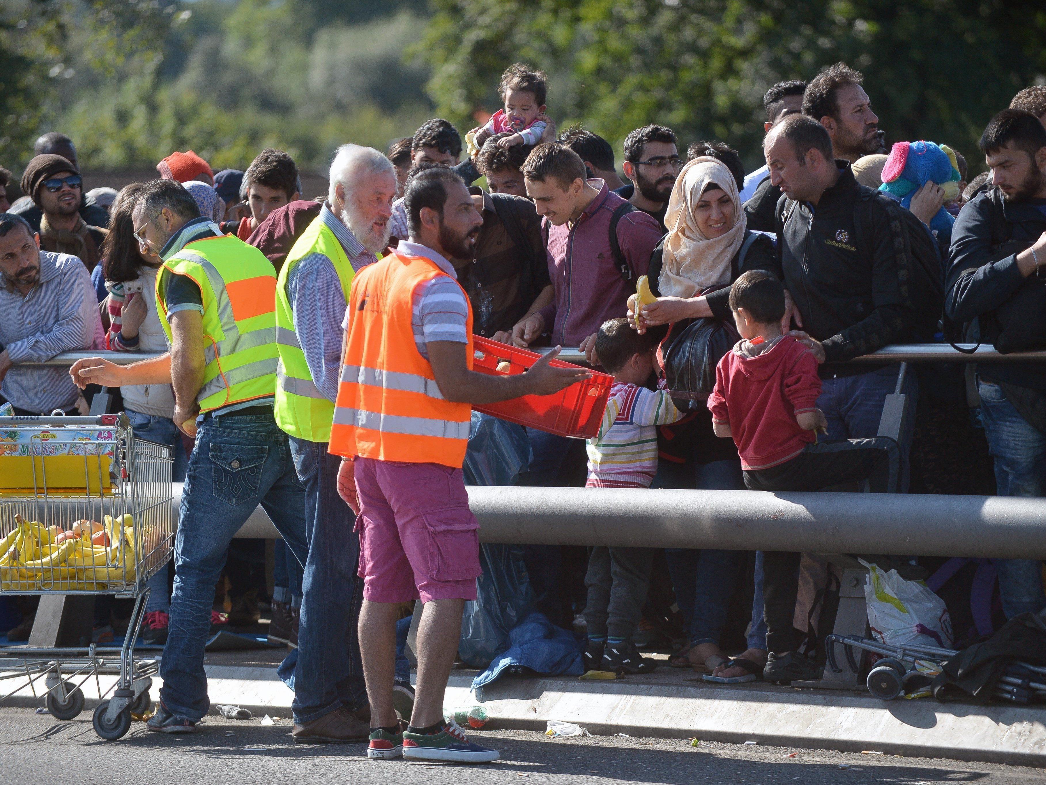 Flüchtlinge warten am österreichisch-deutschen Grenzübergang Freilassing.