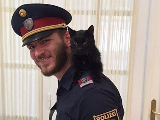 Einer der Polizisten mit der entwischten und geretteten Katze