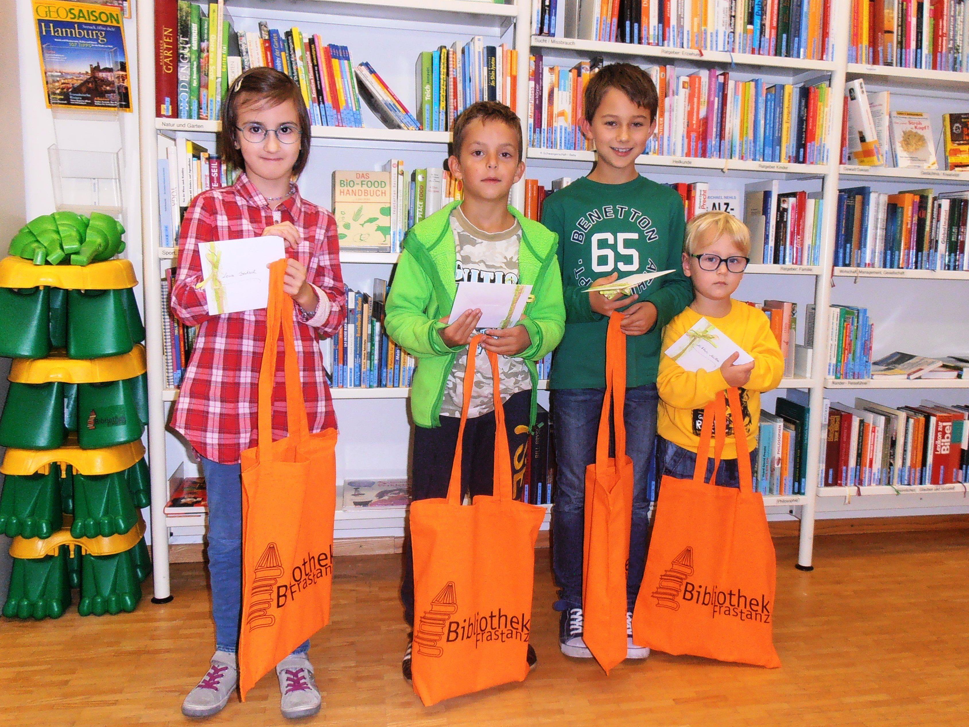 Die Kinder freuen sich über Buchgutscheine und eine neue Bibliothekstasche mit