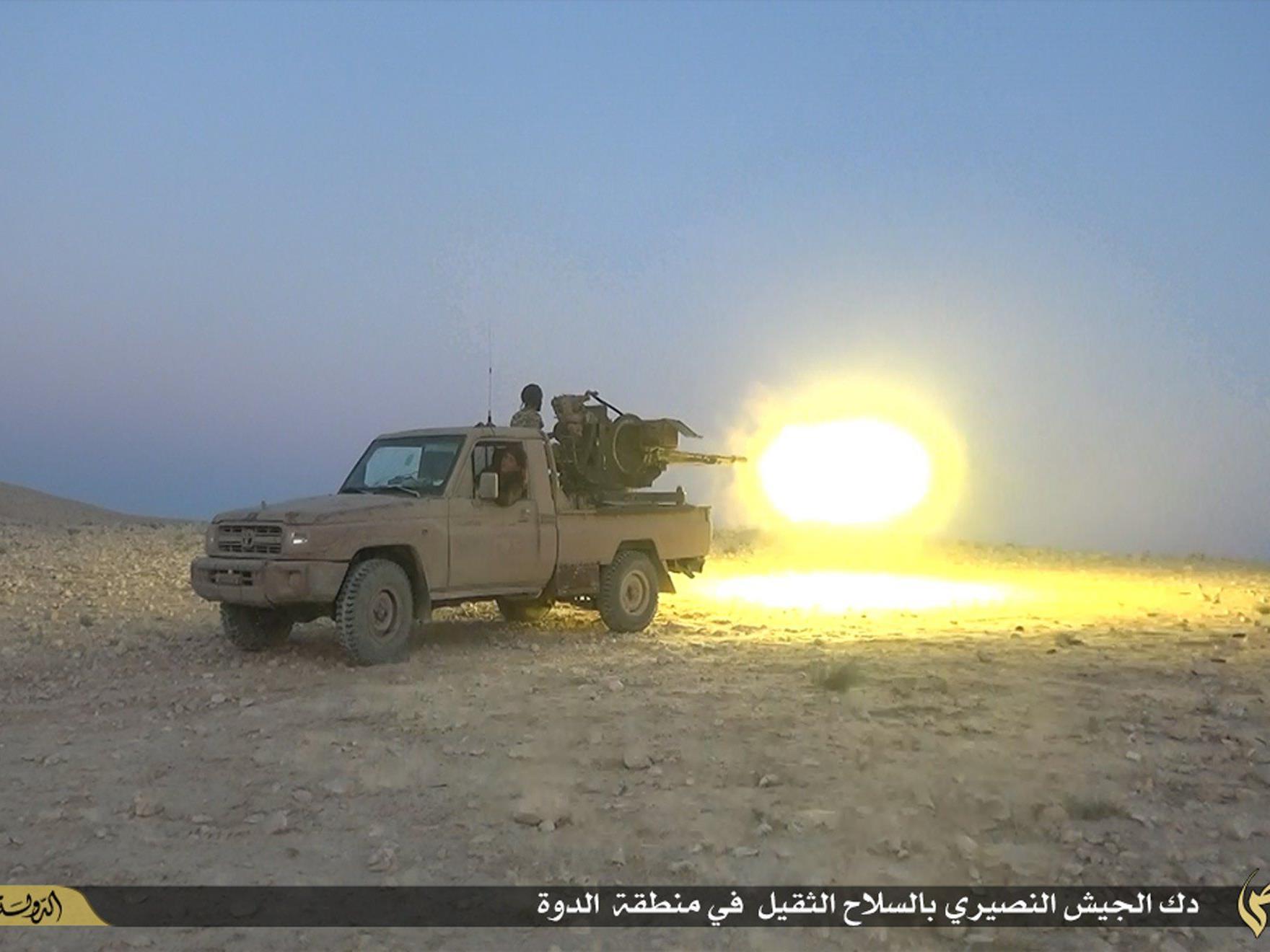 Ein Kämpfer der IS feuert in Homs auf Kämpfer des Assad-Regimes.