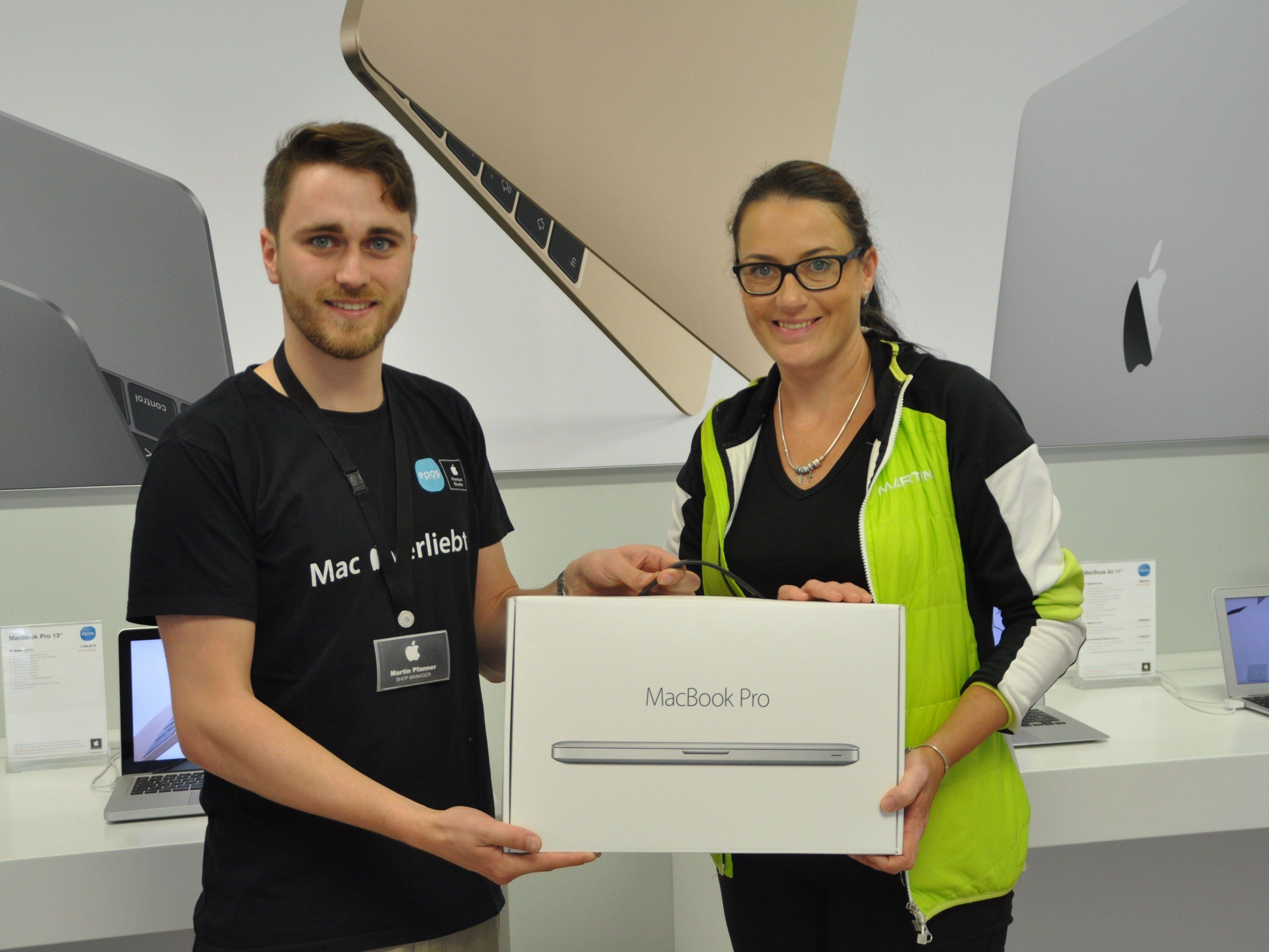 Epos Mitarbeiter Martin Pfanner übergibt Tischlein Deck Dich und Stunde des Herzens Koordinatorin Ines Fritsche ein Mac Book pro