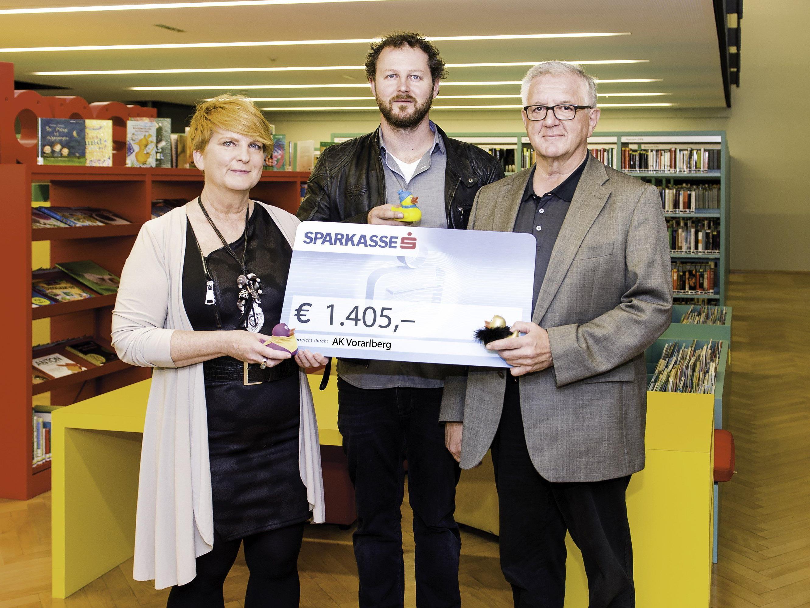 """v.li.: Ulrike Keckeis, AK-Bibliothek Feldkirch, übergibt den Scheck an David Kessler und Franz Abbrederis vom Verein """"Netz für Kinder"""".."""