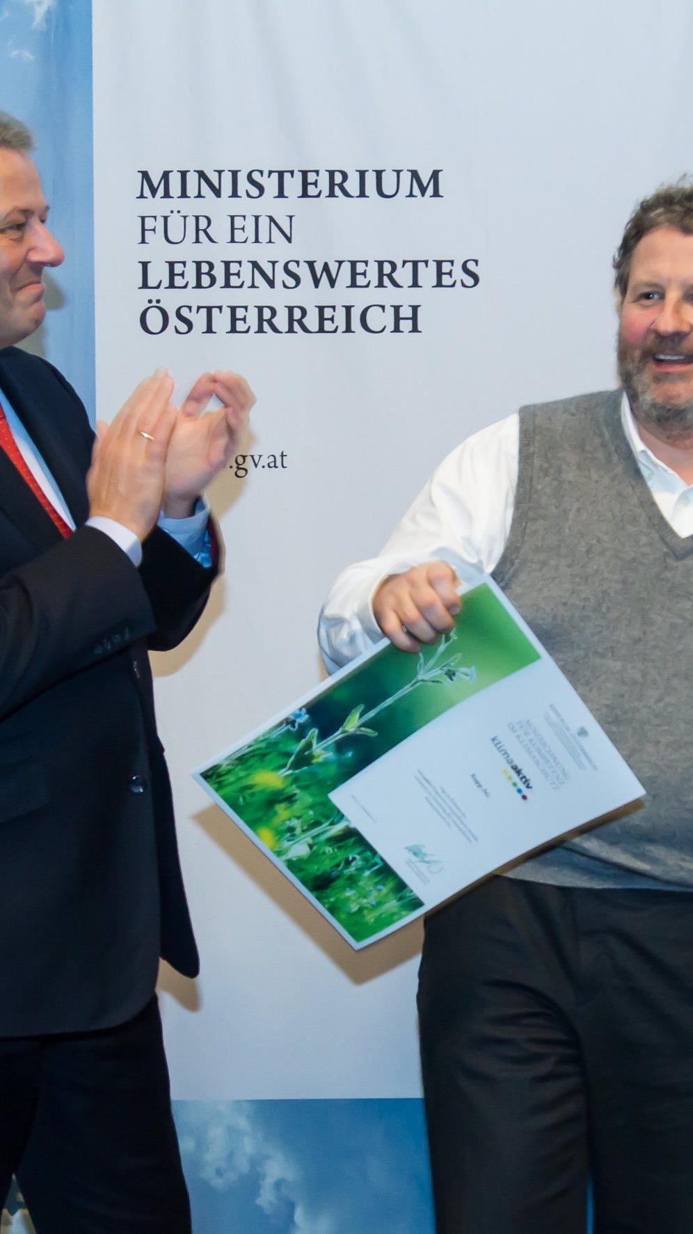 """Umweltminister Andrä Rupprechter übergibt Vorstandsvorsitzendem Josef Rupp die Auszeichnung für """"Kompetenz im Klimasschutz""""."""