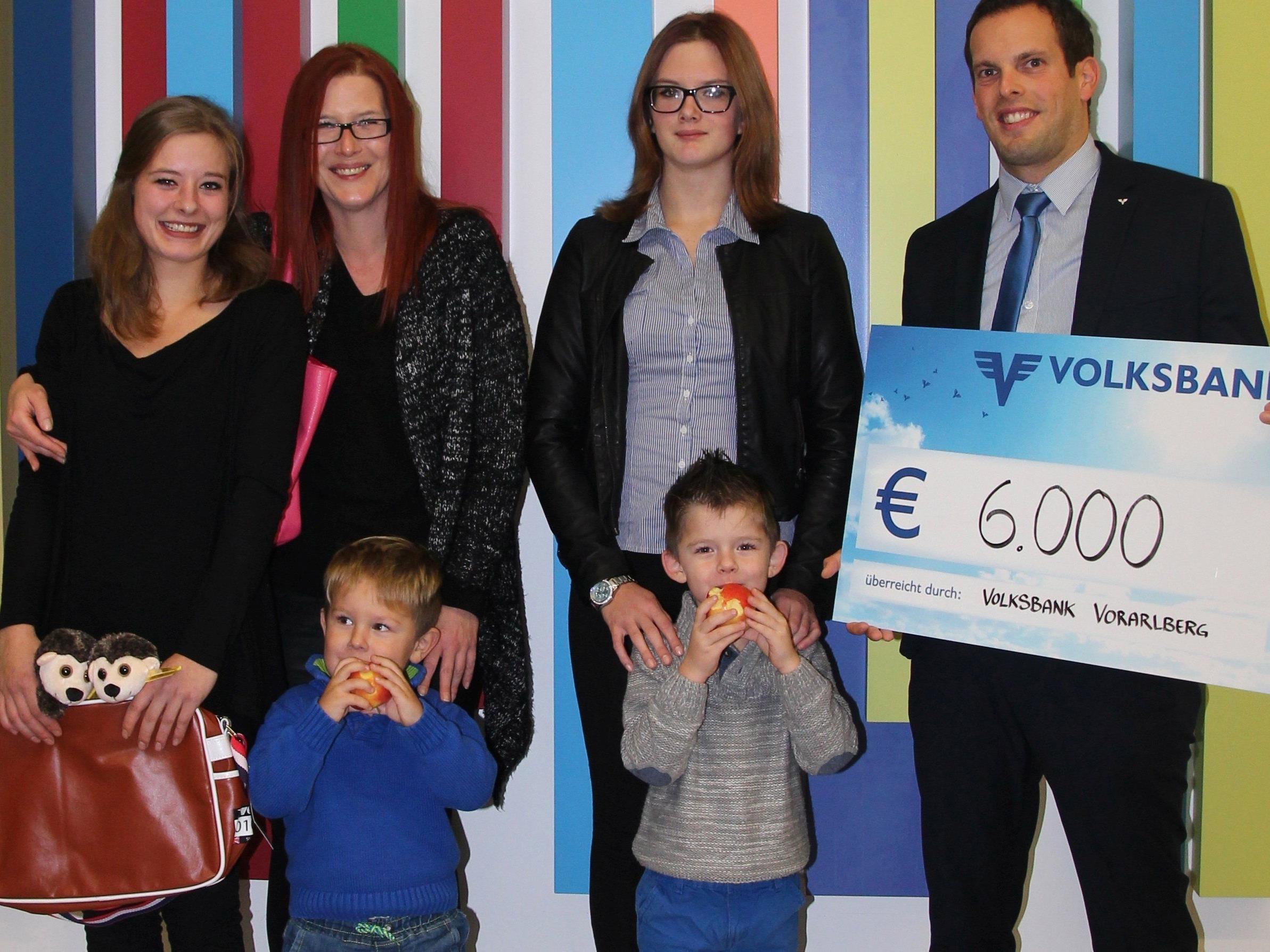Kundenberater Jürgen Boll mit einer der Familien bei der symbolischen Scheckübergabe in der Volksbank Vorarlberg Zentrale in Rankweil.