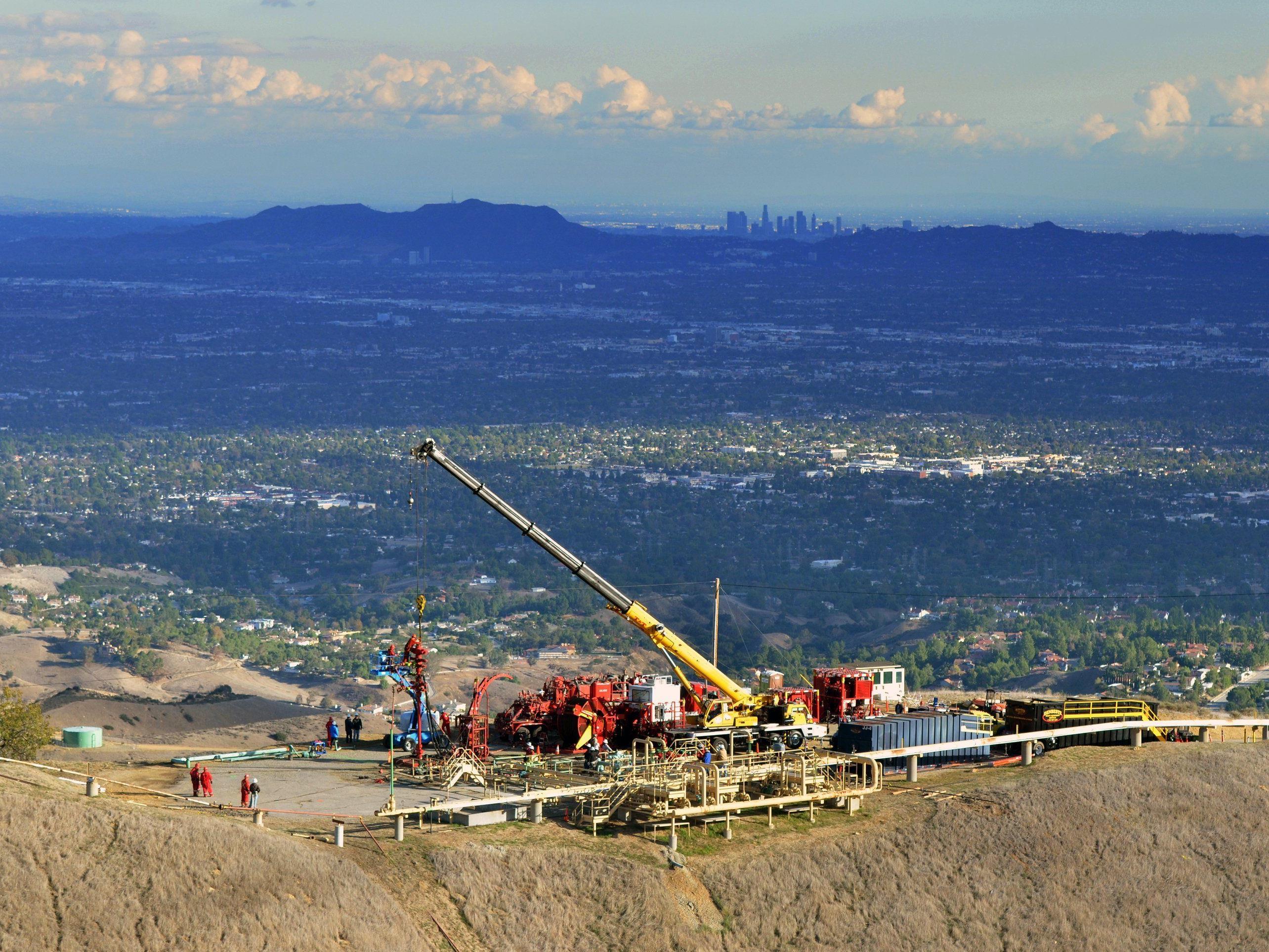 Arbeiter versuchen das Gasleck zu schließen - im Hintergrund die Skyline von Los Angeles.